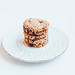 Stacked vegan banana oatmeal cookies with chocolate chips on white background
