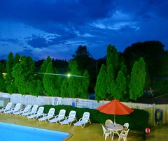 Bleu (Robert Saucier) Tags: capecod piscine swimmingpool ciel sky nuages clouds vert green arbres trees chaises chairs parasol table clôture fence orange ballon img4036 motel dennisport