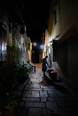 Hoi An, Vietnam (Michelle Tuttle) Tags: hoian vietnam light dark shadow powerful pavement blocks buildings asia woman man disabled lights glow