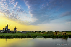 Sunset at the Zaanse Schans (Koelman2008) Tags: netherlands holland zaandam zaanse schans meadow meadows grassland grass water river reflection golden hour sunset sun gold sky clouds cloud