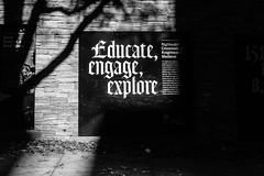 Educate Engage Explore_DSF2083 (Punk Dolphin) Tags: newyorkcity newyork manhattan blackandwhite bw blackandwhitephotography shadows light street bricks sign signage tree sidewalk fujix100f fujifilmx100f