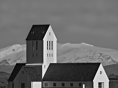 Hekla Volcano behind Skaholt Cathedral (joiseyshowaa) Tags: church black white bw gateway hell steeple stratovolcano tower roof scenery mountain snow background windows prison judas witches ridge heklugjá bishop diocese religion history historic
