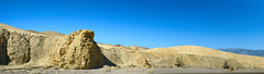 Along Furnace Creek Wash (wyojones) Tags: california furnacecreekwash deathvalleynationalpark streambed cobbles pebbles gravel wash ephermalstream sedimentaryrocks miocene furnacecreekformation mudstone conglomerate geology sky desert