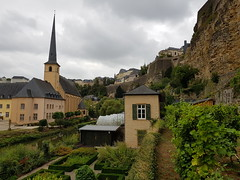 Luxembourg City, Luxembourg (Shaun Smith-Milne) Tags: luxembourg luxembourgcity luxemburg luxemburgstadt stadt ville city grandduchédeluxembourg grandduchyofluxembourg capitale capital capitalcity europe europa birdseye fromabove peaceful paisible nature greenery green greenspaces verdoyant espacevert garden gardens jardin jardins allotments church religion historic heritage églisesaintjeandugrund église saintjohnschurch spire flèche path pathway chemin casemates casematesdubock eau fleuve rivière wasser water river alzig alzette alzetteriver plants gardening rock rocks falaise cliff cliffs falaises vallée valley grund shed