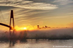 Foggy sunrise by river (james c. (vancouver bc)) Tags: red skyline silhouette yellow ripple riverbank riverside river suspension cable bridge tower reflection hill hilltop fog sunlight tree foggy cloud vivid sunrise peak vapor scenery orange light morning woods picturesque sun misty color colour autumn fall colorful marvelous mist apartment highrise outdoor humidity sky dawn golden scene nature landscape woodland