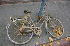 Abandoned? (Jumpin'Jack) Tags: rusty crusty bike bicycle lying onthe floor chained tothe lamp post witha heavy rusted chain sidewalk pavement texture fallen leaves abandoned