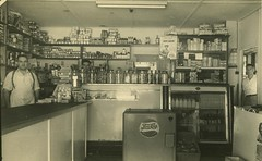 Shopkeepers in the Brisbane suburb of Stafford, 1952 (State Library of Queensland, Australia) Tags: queensland statelibraryofqueensland suburbs suburbia houses shop store milkbottles pepsi shopkeeper cornerstore
