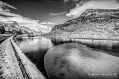 Winter at Ogwen Lake (Adrian Evans Photography) Tags: snowdonia winter idwal water a5 lake snow ogwenvalley wales road tree uk curve northwales sky wall ice nantffrancon landscape lakeogwen ogwen mono outdoor clouds landmark penyrolewen highway adrianevans valley building ogwenlake boathouse snowdonianationalpark blackandwhite mountain frozen