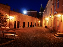 City at Night (docwiththecamera) Tags: building church lampost lamp alley sunstar person bench night city