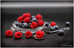 Berries are the spice of life (Heathcliffe2) Tags: art stilllife raspberry raspberries blueberry blueberries fruits berries colour black blue red food nature spoon glass dish macro droplets