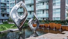 2018 - Vancouver - Eyes on the Street (Ted's photos - For Me & You) Tags: 2018 bc britishcolumbia cropped nikon nikond750 nikonfx tedmcgrath tedsphotos vancouver vancouverbc vancouvercity vignetting eyesonthestreet eyesonthestreetsculpture eyesonthestreetstainless eyesonthestreetstainlesssteelsculpture stainlesssteelsculpture fountain waterfountain mariekhouri mariekhourisculpture mariekhouristainlesssteelsculpture publicart art charlottewall charlottewallsculpture charlottewallstainlesssteelsculpture umbrella decks balconies pond reflection waterreflection deck stainlesssteel janejacobs grass park parkscene wooddeck decking waterfeature eyes two pair duo cans2s canada