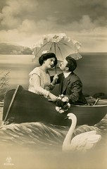 Lovey-Dovey Couple in Boat (Alan Mays) Tags: ephemera postcards realphotopostcards rppc photos photographs foundphotos portraits studiophotos backdrops studioprops boats rowboats studioboats ships water waves wakes swans birds animals clouds lakes men women clothes clothing jackets ties neckties suits dresses couples loveydovey love affectionate romantic looks looking parasols umbrellas flowers bouquets amusing humor humorous funny antique old vintage photographicamusements vptp
