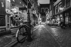 Down on the Street (McQuaide Photography) Tags: haarlem noordholland northholland netherlands nederland holland dutch europe sony a7riii ilce7rm3 7rm3 alpha mirrorless 1635mm sonyzeiss zeiss variotessar fullframe mcquaidephotography lightroom adobe photoshop tripod manfrotto night nacht nightphotography stad city urban lowlight architecture outdoor outside illuminated street straat warmoesstraat window wideangle wideanglelens groothoek building longexposure oldstreet old oud character traditional authentic streetlight atmosphere sfeer nopeople cobblestone cobbles blackandwhite bw mono monochrome bike bicycle fiets shop winkel