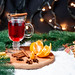 Christmas background with a glass of mulled wine, tangerines, ginger cookies, Christmas tree and garlands