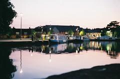 Stratford upon Avon, at dusk (Cogitozoa) Tags: longboat canal dusk water reflection sunset streetlight stratford upon avon calm mirror england analog analogue 35mm film canon canonet ql17 giii rangefinder agfa vista evening