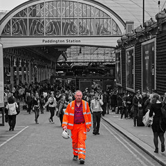 Tango Man (Geoff Henson) Tags: selectivecolour colourpopping orange tango man workman builder overalls helmet highvisibility paddington london station people passengers travellers building architecture sign billboard