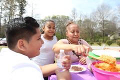 Silvìa Abila, right, serves mexican food to her grandchildren, Christian Canales, left, and Jennifer Mejia, middle, in Robinson Park in Greensboro, Georgia. Abila gets to spend lots of time with her grandchildren through the dance group.