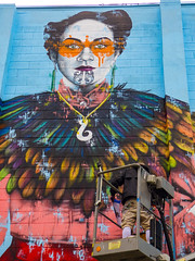 Kaitaki by Fin Dac (Steve Taylor (Photography)) Tags: kaitaki findac oiyou theguardian ashleighsagar moko feathers art graffiti mural streetart colourful orange man woman lady newzealand maori nz southisland canterbury christchurch city cherrypicker earrings mask ewp awp socks artist