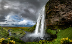 Seljalandsfoss-2 (Bernd Thaller) Tags: rangárþingeystra suðurland island is seljalandfoss waterfall water flowers grass cliff rocks clouds landscape