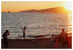 Two Women Holding Up the Sun (HereInVancouver) Tags: sunset people beach mountains water ocean pacific women posing portraits holdingupthesun reflection englishbay vancouverswestend thingstodobythewater candid canong3x city urban park vancouver bc canada