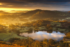 Loughrigg tarn winter sunrise glow (John Finney) Tags: woodland england landscape nature cumbria ruralscene englishlakedistrict weather morning northwestengland valley sunrise loughrigg mist fog loughriggtarn