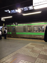 Rapid Airport Express with People (sjrankin) Tags: 25september2018 edited hokkaido japan gif animatedgif sapporo jrsapporostation trainstation buildings skyline downtown train platform crowd commute people rapidairportexpress