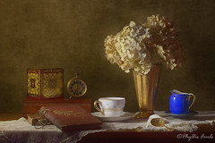 Still life quiet moment (Phyllis Freels) Tags: phyllisfreels book clock creamer cup driedflowers glasses gold hydrangea lace red spectacles spoon stilllife tin vase vintage