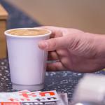 Mann greift nach Cappuccino in Pappbecher thumbnail