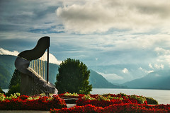 """The kiss of the muse"" (echumachenco) Tags: fountain sculpture art harp lyre flower flowerbed red green tree lake water sky cloud cloudy mist mountain mountainside mountains alps september ossiach ossiachersee carinthia kärnten austria österreich outdoor landscape scenery nikond3100"