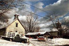 50-046 (ndpa / s. lundeen, archivist) Tags: nick dewolf nickdewolf color photographbynickdewolf 1973 1970s film 35mm 50 reel50 winter maine centralmaine snow snowy snowfall newengland ontheroad roadtrip newhampshire rural sky clouds building house home powerlines snowbanks roadside school schoolhouse church buildings trees branches newidea newideafarmequipment sign truck pickuptruck car vehicle automobile ford driveway farmequipment trip vacation wintertrip wintervacation