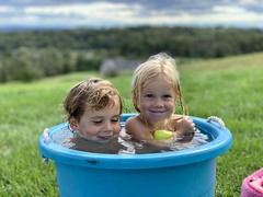 The twins enjoy their hot tub bucket as the cold wind blows (dionhinchcliffe) Tags: moblog iphonepics