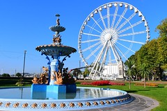 Fountain and Wheel (gillybooze) Tags: ©allrightsreserved vista sky wheel fountain water statue grass tree streetlamps trees flower architecture flowers monument fair torquay outside shadows outdoor reflections park