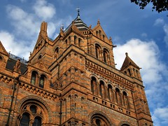 East tower, Natural History Museum, Cromwell Road, South Kensington, London SW7. (edk7) Tags: olympusomdem5 edk7 2018 uk england london londonsw7 royalboroughofkensingtonandchelsea southkensington cromwellroad naturalhistorymuseum architecture building oldstructure alfredwaterhouse1881 victorian terracotta romanesquerevival gradeilisted tower east arch column gargoyle sculpture fauna sky cloud polychrome chimney weathervane dentil colonnade