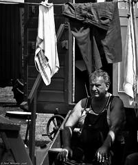 Washday Blues (Neil. Moralee) Tags: neilmoralee steamrally2018neilmoralee man wash washday clothes washing caravan traveller line drying old mature face portrait neil moralee olympus omd em5 black white bw bandw blackandwhite mono monochrome poor poverty overalls bib brace braces sunshine shadow bright brite dark alone waiting patient history jeans vest towel