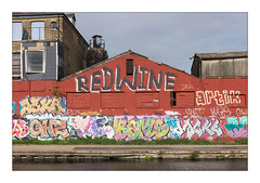 Graffiti (Edwin, Bams etc), East London, England. (Joseph O'Malley64) Tags: edwin bams graffiti urbanart publicart freeart thebuiltenvironment newtopography newtopographics buildings structures eastlondon eastend london england uk britain british greatbritain art artists artistry artworks industrialbuildings brickwork bricksmortar cement pointing londonbrick corrugatedsteelroofingpanels roofingslates windows blockedwindows steelframedwindows victorian victorianbuilding shed wall walls towpath canal canalised concrete blockpaving nettles weeds steelpilings silo tank louvre vent railings drainpipe chimneys buddleia buddleiaflorets urban urbanlandscape urbanarchitecture architecture fujix fujix100t aerosol cans spray paint accuracyprecision redwine