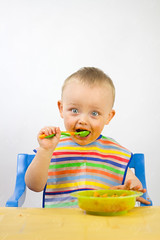 Infant Eating His First Meals (the UMF) Tags: againstwhite brightcolors individuals infant isolatedonwhite plainbackground studiolighting vertical whitebackground baby babyboy colorful copyspace dinner eating eatingdinner food foodonface happy lookingatcamera lookingintocamera messy messybaby messyeating portrait selectivefocus shallowdepthoffield spacefortext studioshot