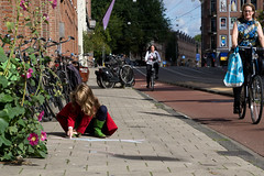 Amsterdam, City of Freedom (Adrià Páez) Tags: amsterdam city freedom capital holland northholland noordholland nederland the netherlands europe street bike path cycling bicycles girl kid child painting floor plant flowers canon eos 7d mark ii streetphoto photography