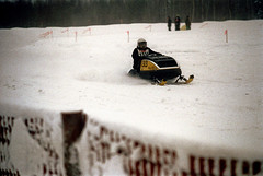 50-353 (ndpa / s. lundeen, archivist) Tags: nick dewolf nickdewolf color photographbynickdewolf 1973 1970s film 35mm 50 reel50 winter maine centralmaine snow snowy snowmobile snowmachine race snowmobilerace racing course fence racecourse finishline ussa racer driver helmet people onlookers spectators 1313 skidoo trip wintertrip vacation snowfence bib