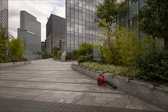 shiodome-7083-ps-w (pw-pix) Tags: walkway elevatedwalkway pedestrianwalkway pedestrianoverpass glass tiles tiled blowervac leafblower broom cleaning equipment tools plants shrubs bamboo trees building buildings offices commercial clouds sky grey overcast cloudy neardentsubuilding shiodome minato minatoku tokyo tokyoto japan peterwilliams pwpix wwwpwpixstudio pwpixstudio