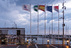 Blowing in the wind (Alicia Clerencia) Tags: flag viento wind embarcadero pier motion largaexposicion longexposure nubes clouds storm tormenta nocturna nighttime bike bicicleta marina boats barcos