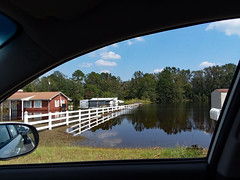 Flooding By A Fence. (dccradio) Tags: lumberton nc northcarolina robesoncounty outdoor outdoors outside sky bluesky cloud clouds cloudformation tree trees greenery leaf leaves branch branches treebranch treebranches alamacroad flood flooding floodwaters florenceaftermath hurricaneflorence mirror sideviewmirror fence whitefence reflection grass lawn ground yard residential residentialflooding house building architecture