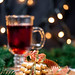 Christmas background with glass of mulled wine, ginger cookies, Christmas tree and garlands