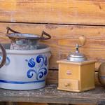 Kaffeemühle und Tontopf vor Holzwand thumbnail