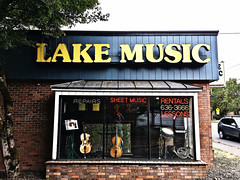 """Lake Music"" (Halvorsong) Tags: music usa oregon signs street road roadside roadtrip photosafari balance frame framed yellow cool instruments storefront america americana old oldschool vintage classic childhood neon tradition band brick wall fun wow explore discover art halvorsong shop sign"