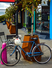Cafe Racer (Steve Taylor (Photography)) Tags: cafe racer helmet art sign chair tableandchairs blue black brown mauve pink man newzealand nz southisland canterbury christchurch newbrighton trees perspective bike bicycle