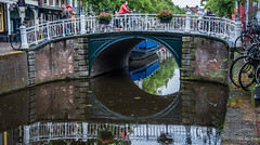 2018 - Delft - Canal - 1 of 4 (Ted's photos - Returns Late November) Tags: 2018 cropped delft nikon nikond750 nikonfx tedmcgrath tedsphotos vignetting canada canalscene bridge canalbridge canalbridgedelft reflection waterreflection brickwall brick bikes bicycles railing people peopleandpaths pathsandpeople