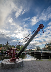 old crane by the water (Mange J) Tags: k3ii magnusjakobsson pentax river sigma1020 sverige sweden blue bridge chilly church cloud crane hole mirror old pentaxart pitoresque reflection sky tourism wood