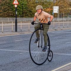 Penny Farthing (Croydon Clicker) Tags: bicycle cyclist bike pennyfarthing road man hat wheels spokes pedals sign barrier cofo47ksen cof047dmnq cof047chon