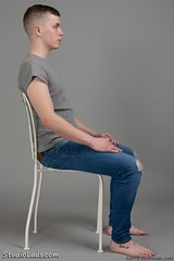 Guy sitting sideways in blue jeans (StudioLads.com) Tags: male model man guy dude youth stud hunk boy lad pose studio photoshoot chair jeans tshirt fashion trendy casual blue hot horny sexy cute fit foot feet barefoot sit sitting