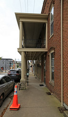 Porch — Nicholasville, Kentucky (Pythaglio) Tags: nicholasville kentucky jessaminecounty building structure historic twostory brick italianate porch twostoryporch sidewalk cars cones segmentalarched hoodmolds corbelling corbelled 22windows dentils columns downspout jsn48